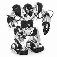 WowWee Robosapien (8083) - полнофункциональная интерактивная игрушка, которая не оставит равнодушным самого взыскательного коллекционера. Модель поражает широким спектром игровых возможностей: умеет петь и танцевать, быстро двигаться, имеет 67 программируемых функций, может играть в футбол, подметать пол, брать и перемещать вещи руками (при том, одна рука для захвата мелких предметов, другая - для более крупных), и даже знает полтора десятка движений кунг-фу. Robosapien 8083 также способен весьма реалистично воспроизводить некоторые человеческие звуки (например, свист или храп). Для более быстрого и плавного перемещения в механизме предусмотрен двухскоростной режим ходьбы.  Характеристика командных функций: прямое управление, комбинационные последовательности, действия с выражением своего отношения, демонстрационные режимы и возможность собственных алгоритмов.  Максимальное время, на которое вы можете запрограммировать своего робота, составляет целых 5,5 часов. «Организм» Robosapien оснащен 7 мини-моторами с 6 подвижными осями, каждый из которых поддерживает индивидуальные настройки, выбранные хозяином. Конечности оборудованы специальными сенсорами, позволяющими роботу обходить препятствия или останавливаться перед ними. Возможно программирование датчиков, чтобы при обнаружении препятствия робот начинал выполнять ранее введенную последовательность команд. В комплекте имеется удобный трансмиттер с необходимым набором кнопок и понятным интерфейсом. Приятной особенностью служит наличие акустического датчика, отвечающего за выполнение команд по хлопку или другому громкому звуку.